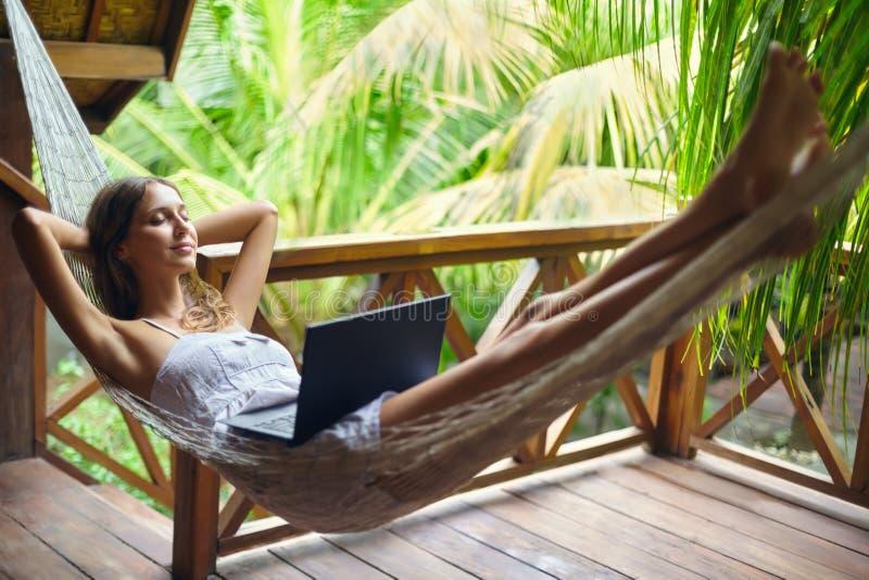 放松在有膝上型计算机的一个吊床的少妇在一热带reso 免版税库存图片