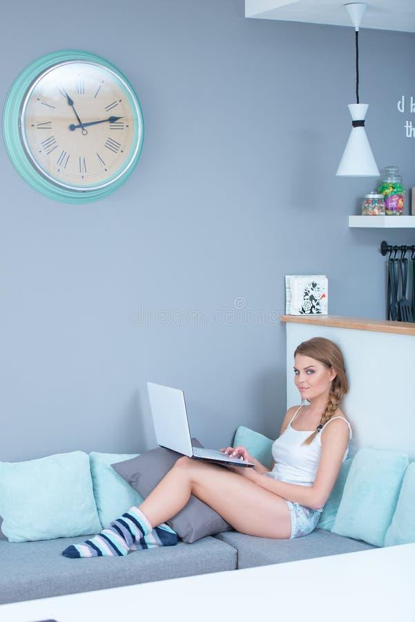放松在有膝上型计算机的一个沙发的美丽的妇女 图库摄影
