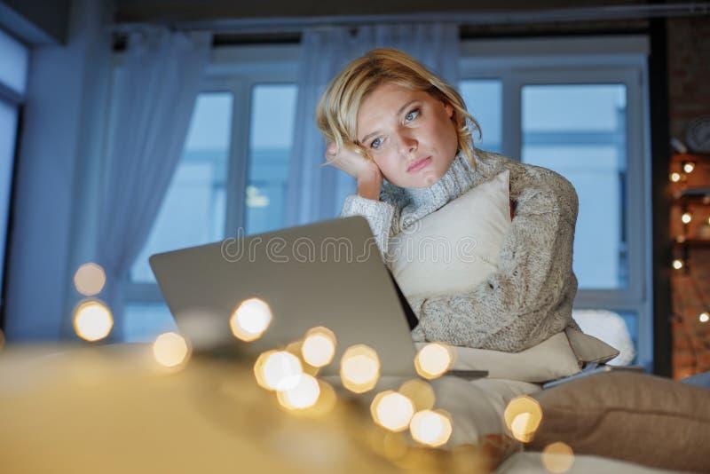 放松在有膝上型计算机的房子的哀伤的女孩 免版税图库摄影