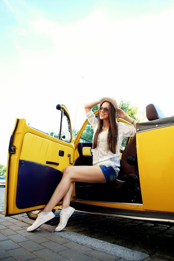 放松在有被日光照射了由后照的路的汽车的少妇在背景中 免版税库存照片