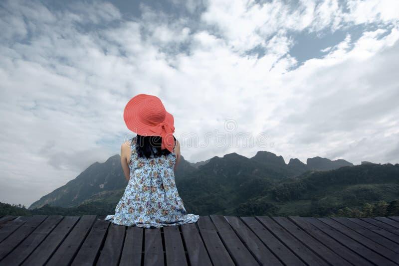 放松在木大阳台的妇女 免版税库存图片