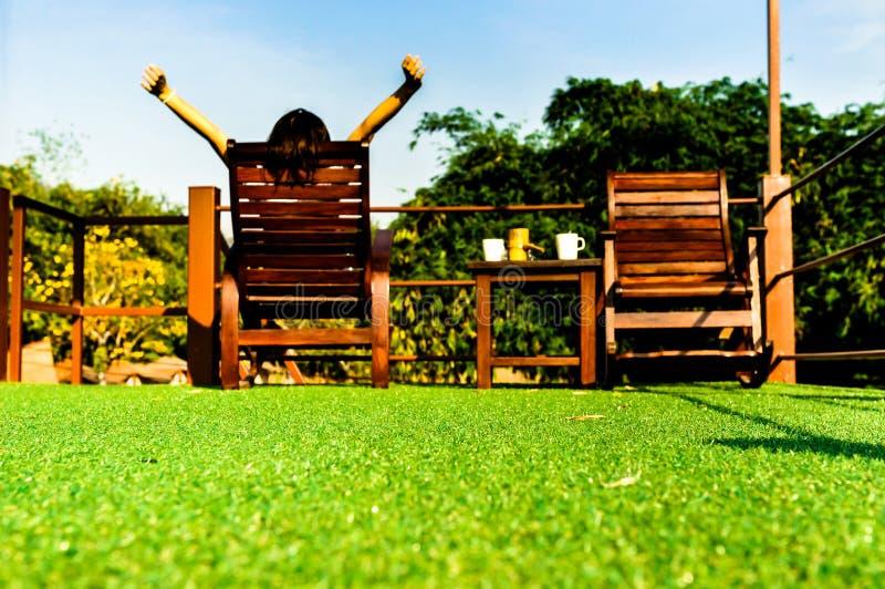 放松在木sunbed在绿色人为草和看蓝天的妇女 免版税库存照片