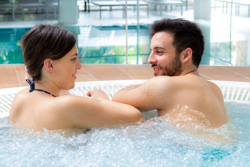 放松在极可意浴缸的年轻夫妇 免版税库存图片
