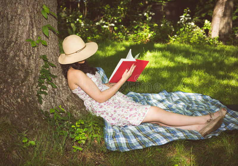 放松在树的妇女读书外面 免版税库存图片