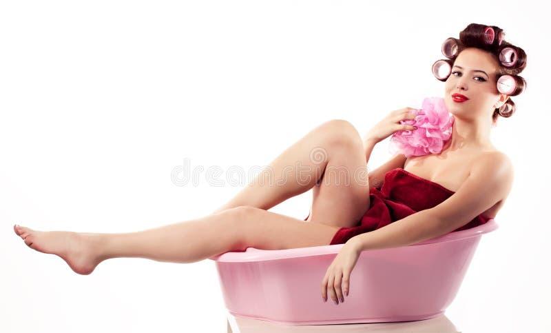 放松在桃红色浴缸的妇女佩带的haircurlers。 Pinup styl 免版税图库摄影