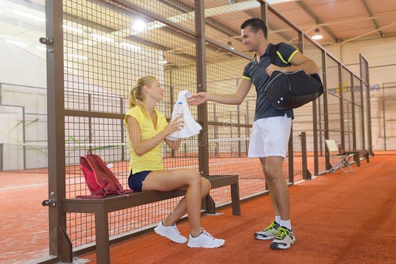 放松在桨网球比赛以后的两个球员 免版税图库摄影