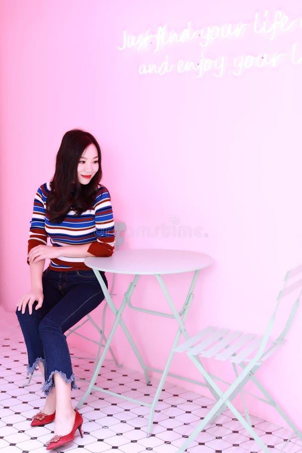 放松在椅子的美丽的亚裔中国年轻女人 库存照片