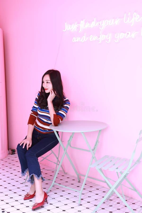 放松在椅子的美丽的亚裔中国年轻女人 免版税库存照片
