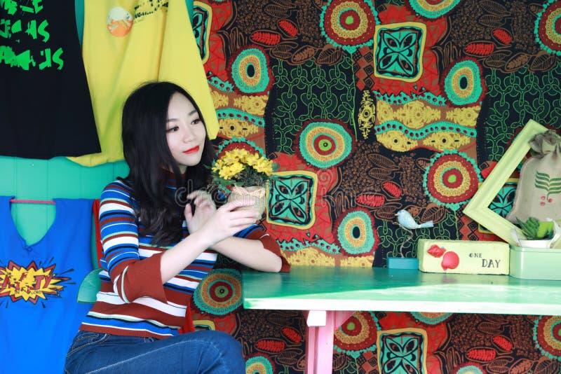放松在椅子的美丽的亚裔中国年轻女人 免版税库存图片