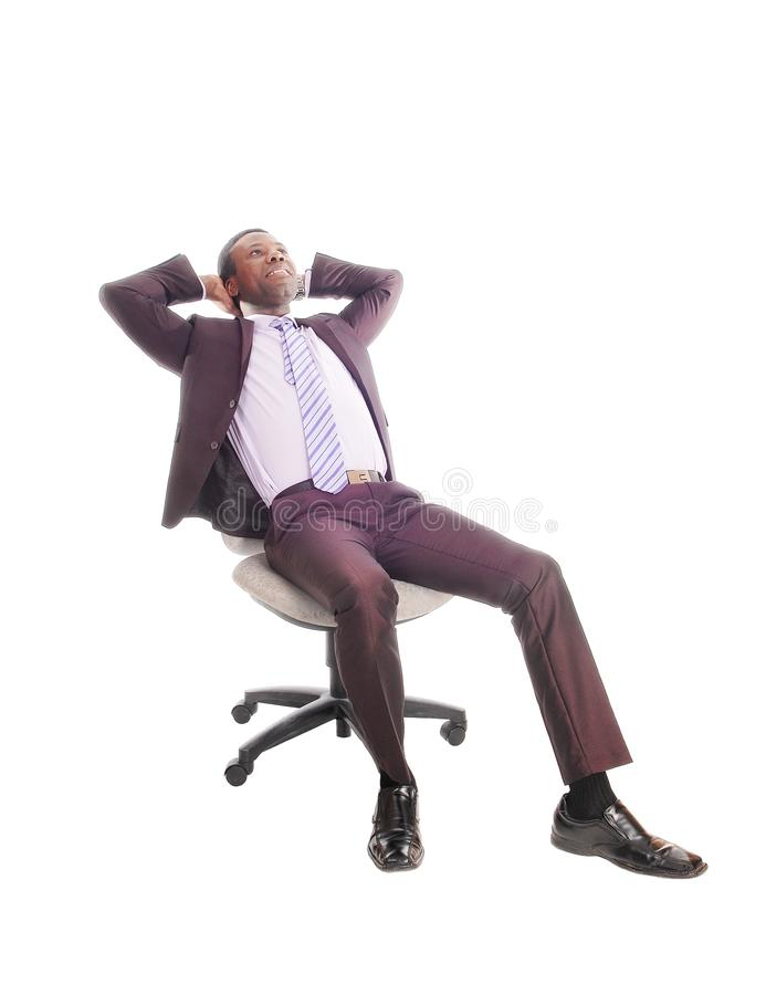 放松在椅子的非洲商人 库存图片