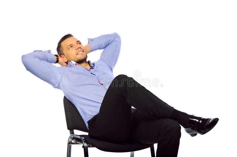 放松在椅子的年轻英俊的人被隔绝在白色backg 免版税库存照片