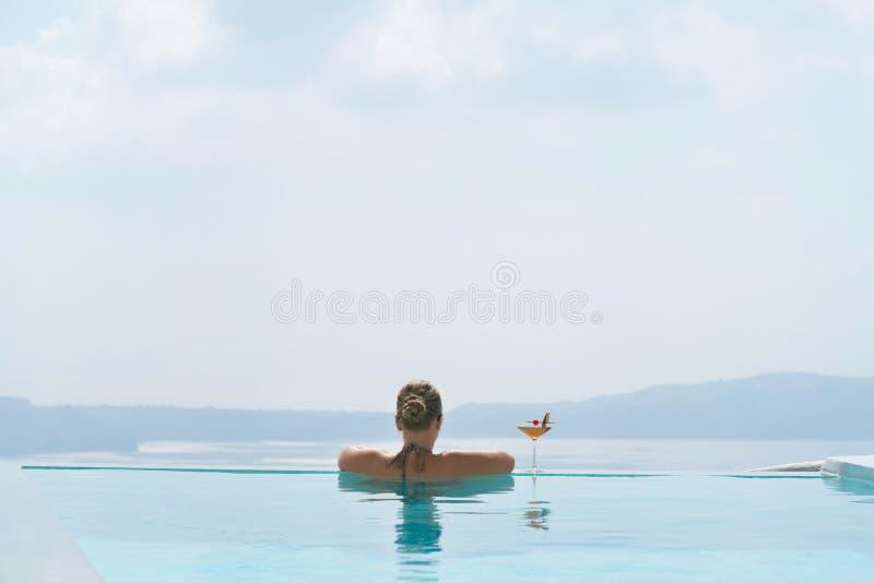 放松在水池的年轻女人有在圣托里尼的一个出色的意见 免版税库存照片