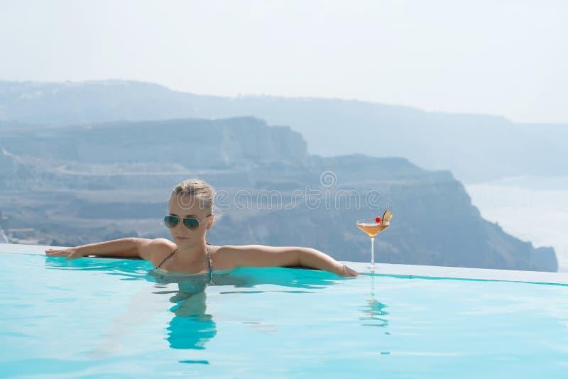 放松在水池的年轻女人有在圣托里尼的一个出色的意见 库存照片