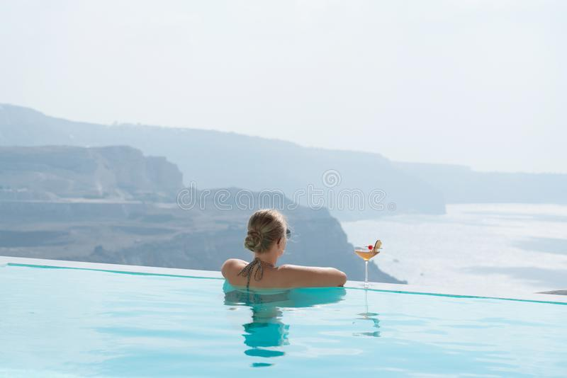 放松在水池的年轻女人有在圣托里尼的一个出色的意见 图库摄影