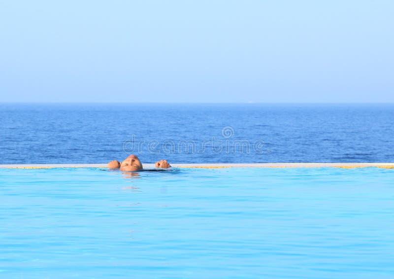 放松在水池的年轻女人由海 免版税库存图片