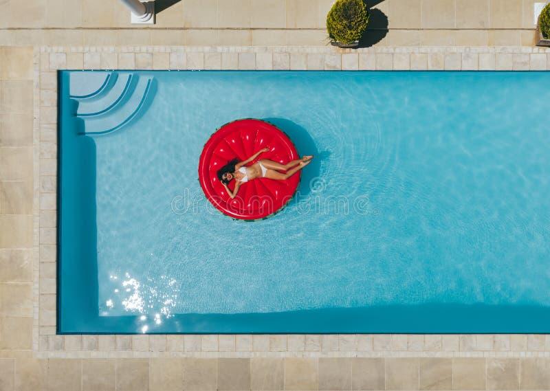 放松在水池的浮动床垫的妇女 免版税库存图片