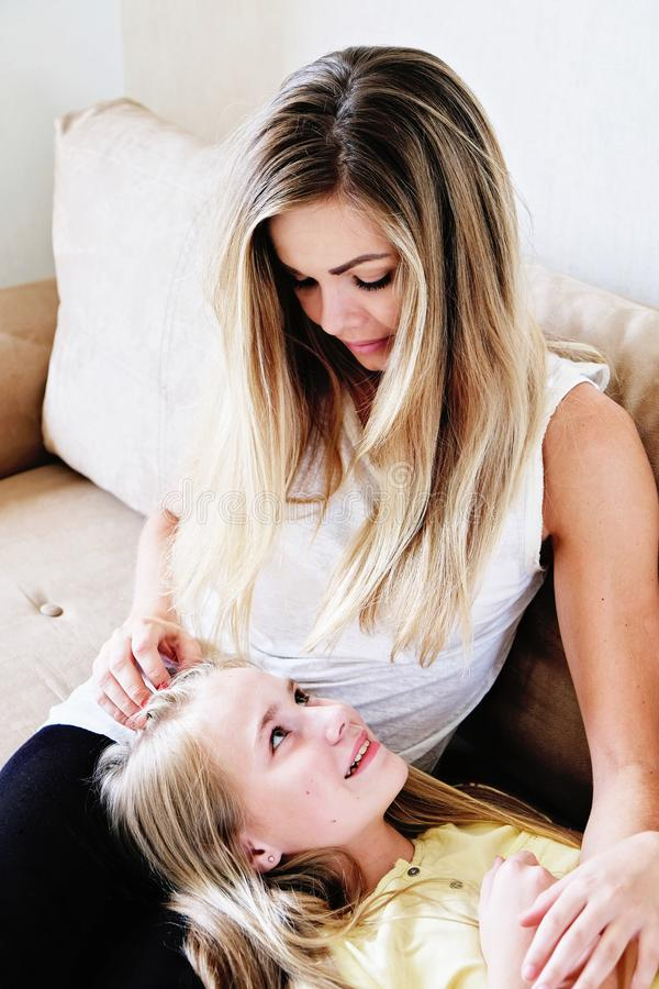 放松在沙发的妈妈和小女孩 图库摄影