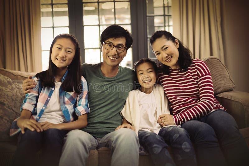 放松在沙发的微笑的家庭在客厅 免版税库存照片