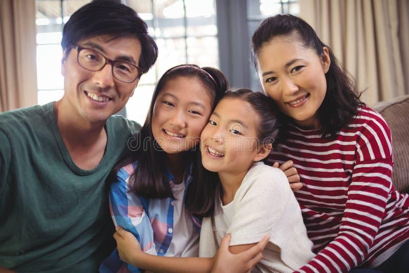 放松在沙发的微笑的家庭在客厅 免版税库存图片