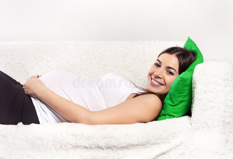 放松在沙发的怀孕的深色的妇女 图库摄影