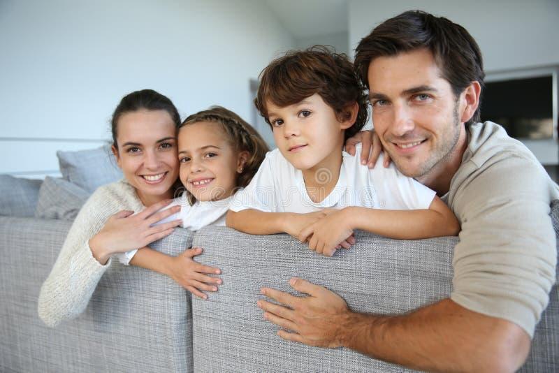 放松在沙发的愉快的年轻家庭 免版税库存照片