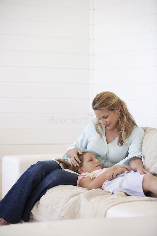 放松在沙发的母亲和女儿 库存图片