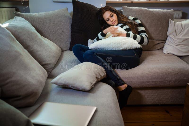 放松在沙发的沉思和孤独的少妇 库存图片