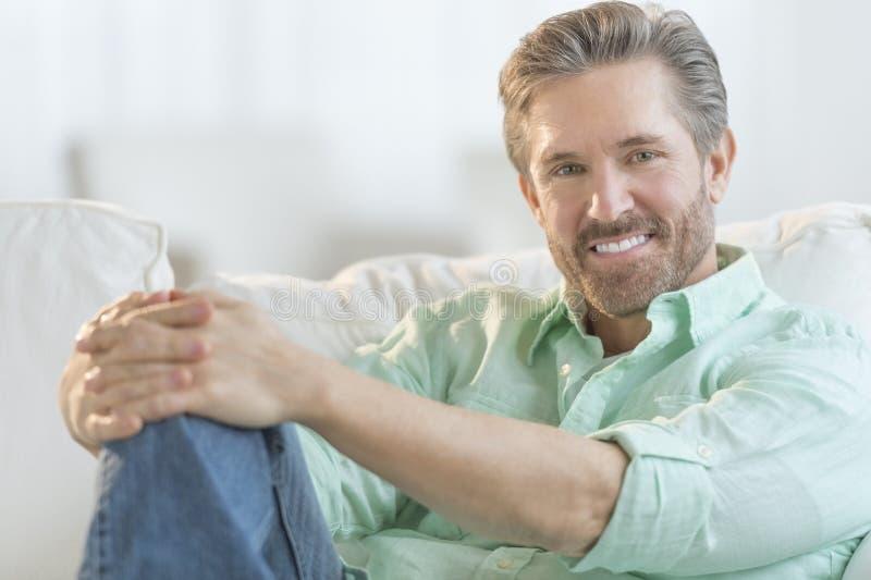 放松在沙发的英俊的成熟人 免版税库存图片