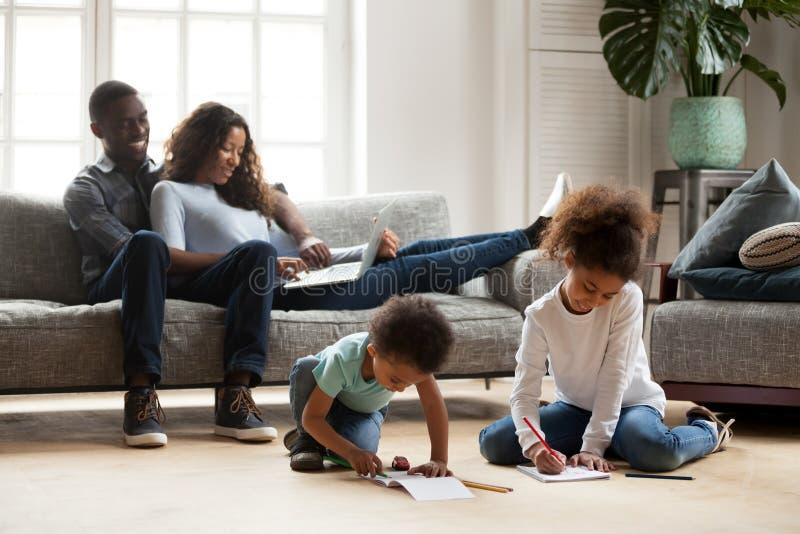 放松在沙发的非洲父母,当一起演奏dra时的孩子 免版税库存图片