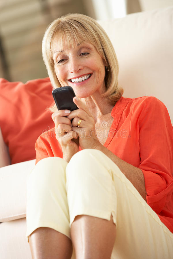 放松在沙发的高级妇女发送正文消息 免版税图库摄影