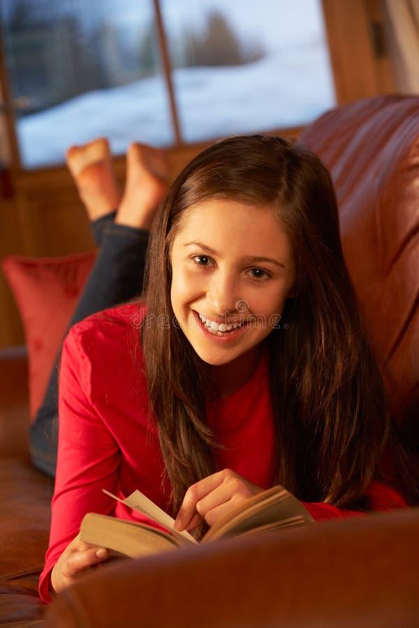 放松在沙发阅读书的十几岁的女孩 库存图片