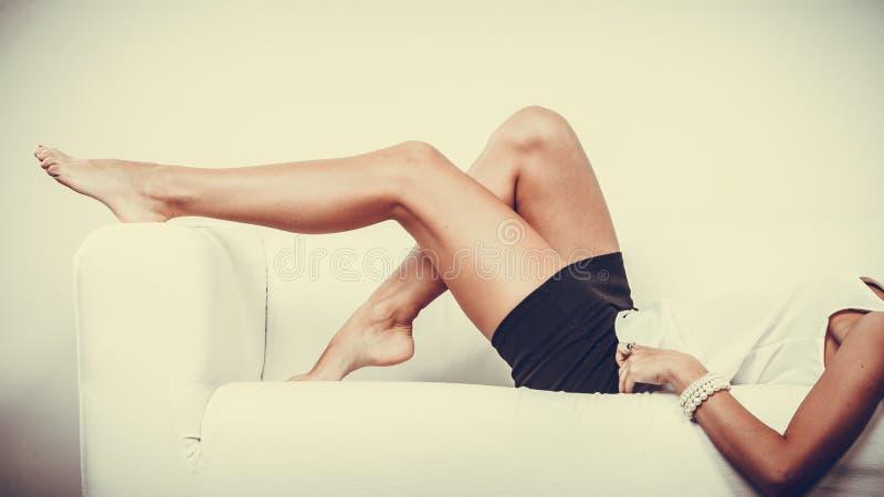 放松在沙发,秀丽女性腿的女孩 库存照片