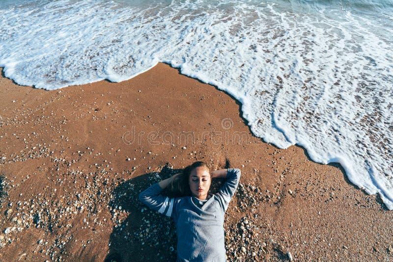 放松在沙子由海波浪,秋天海滩概念 免版税库存照片