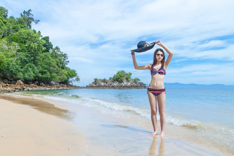 放松在沙滩,旅行暑假概念的比基尼泳装和海滩帽子的美丽的年轻亚裔妇女 库存图片