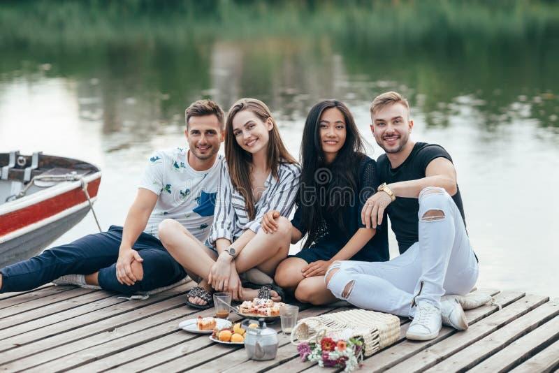 放松在河木码头的小组愉快的年轻朋友 库存照片