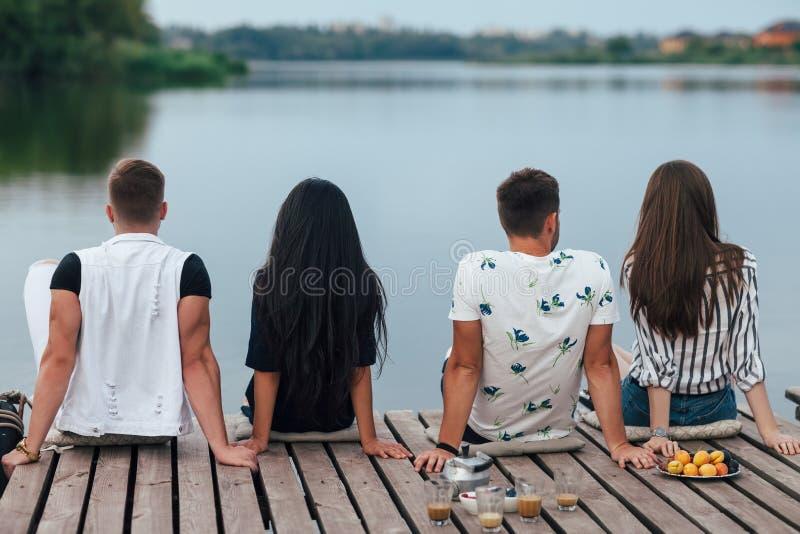 放松在河码头的后面观点的朋友 免版税图库摄影