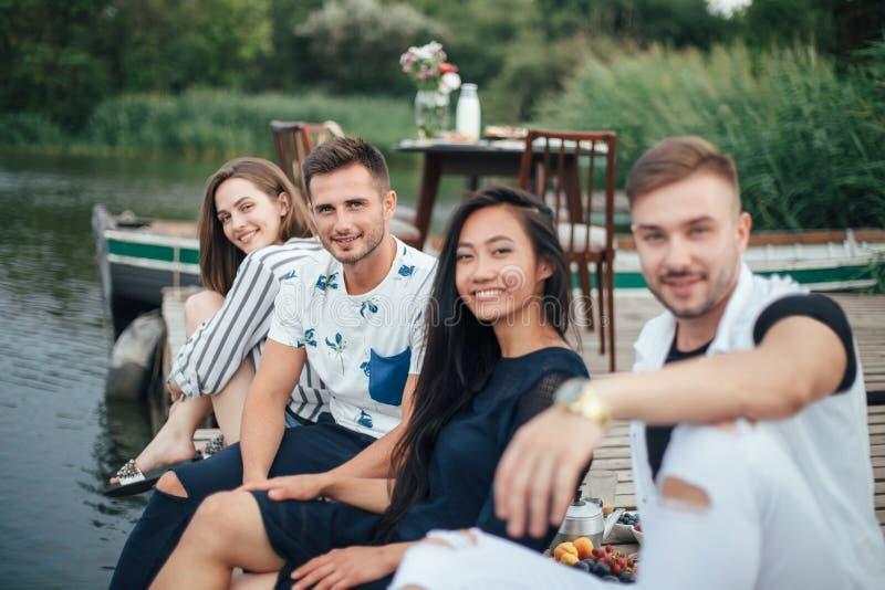 放松在河码头的小组愉快的年轻朋友 图库摄影