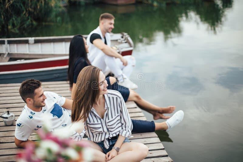 放松在河码头的小组愉快的年轻朋友 免版税图库摄影