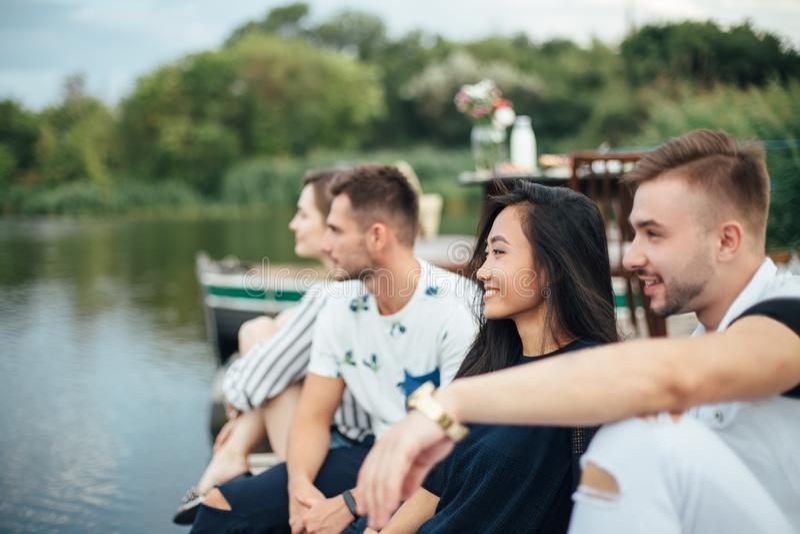 放松在河码头的小组愉快的年轻朋友 免版税库存照片