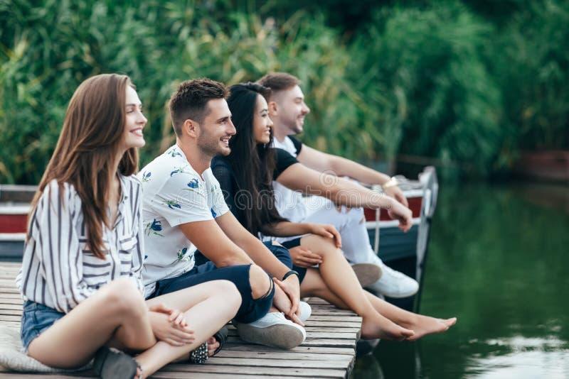 放松在河码头的小组愉快的年轻朋友 免版税库存图片