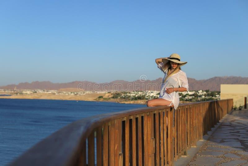 放松在泳装和与在大阳台的轻的海滩礼服的一名性感的美丽的被晒黑的妇女的画象与蓝色海和 图库摄影
