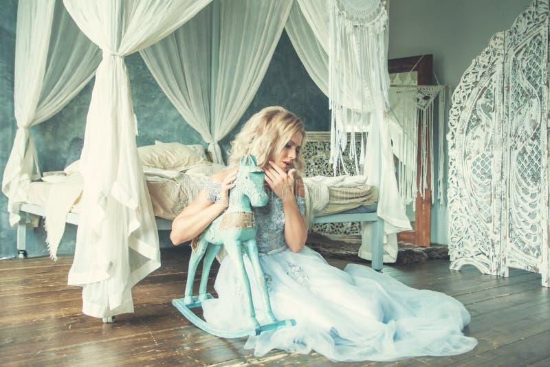 放松在浪漫减速火箭的内部的薄纱礼服的完善的妇女 图库摄影