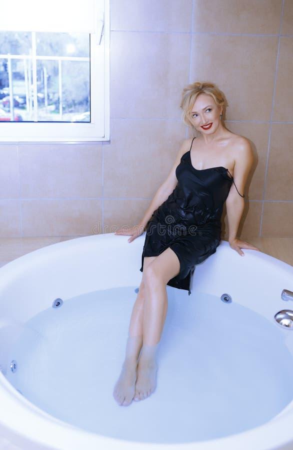 放松在浴的妇女佩带的滑动礼服 免版税库存照片