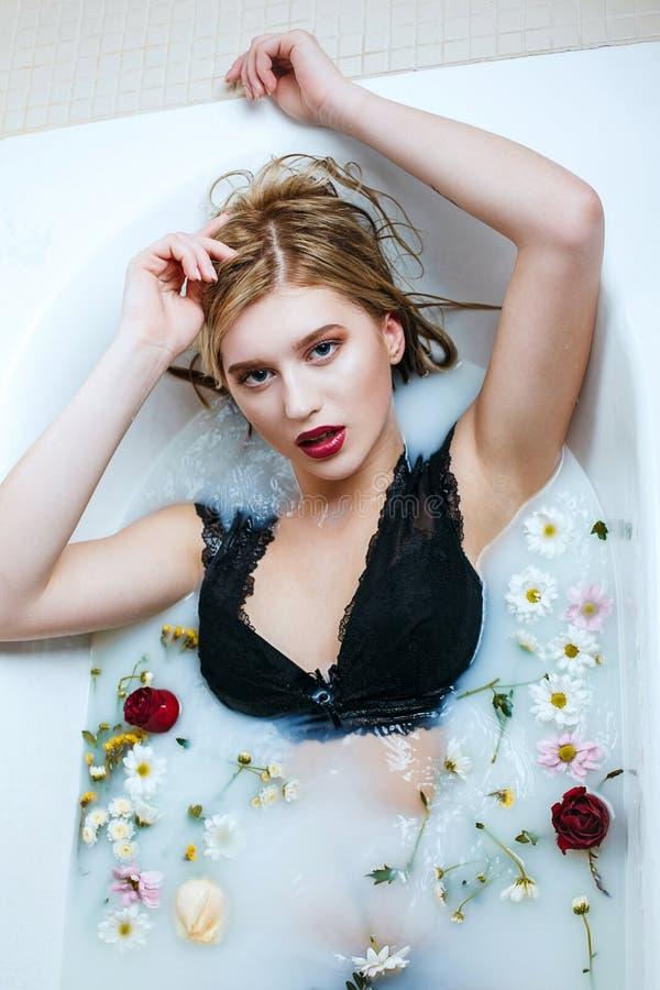 放松在浴的魅力少女佩带的鞋带胸罩用牛奶和花 免版税图库摄影