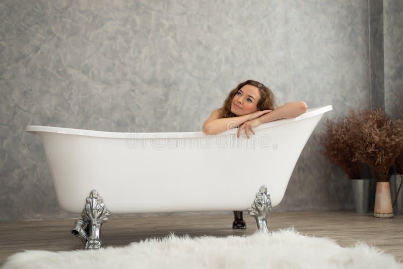 放松在浴缸的微笑的妇女 库存图片