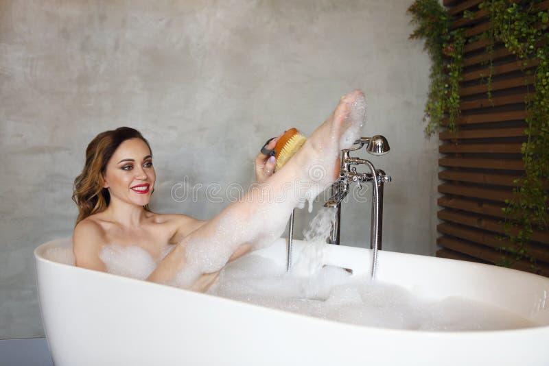 放松在浴缸的愉快的年轻女人 库存图片