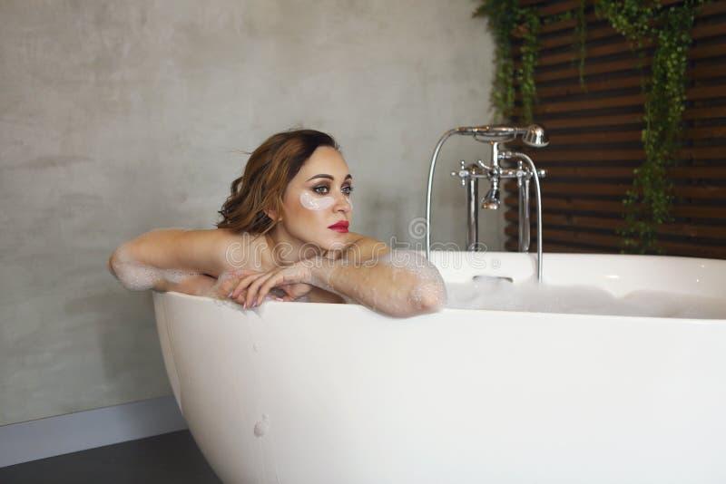 放松在浴缸的愉快的年轻女人 免版税库存照片