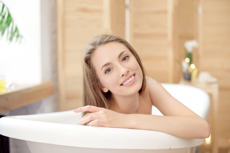 放松在浴缸的美丽的女孩 免版税库存照片