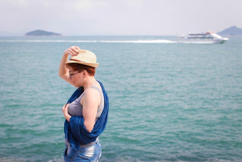 放松在海岸的有风夏日感到好 妇女 免版税库存图片
