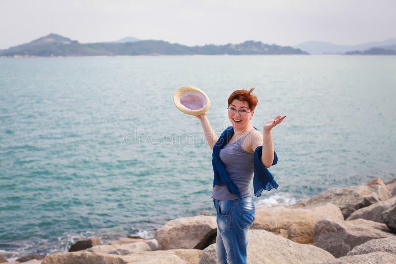 放松在海岸的有风夏日感到好 玻璃和牛仔裤的妇女在海岸走 库存照片